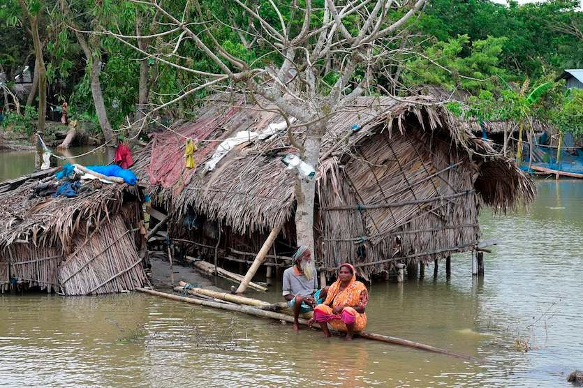 A marooned elderly couple sit on a log close to their home surrounded by high waters in Khulna on Saturday, May 4, 2019, after the storm surge from Tropical Cyclone Fani indundated parts of coastal Bangladesh