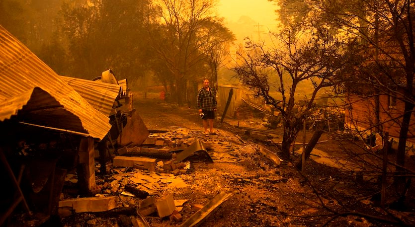 Gary Hinton stands amongst rubble after fires devastated the New South Wales town of Cobargo, 12/31/19