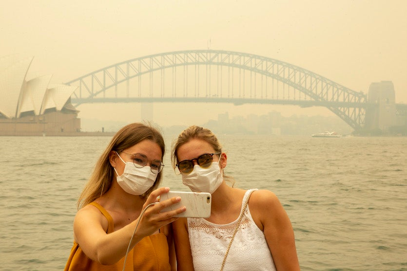 German tourists Julia Wasmiller (left) and Jessica Pryor take a selfie of downtown Sydney from the rock feature known as Mrs. Macquarie's Chair, wearing face masks due to heavy smoke, on Thursday, December 19, 2019
