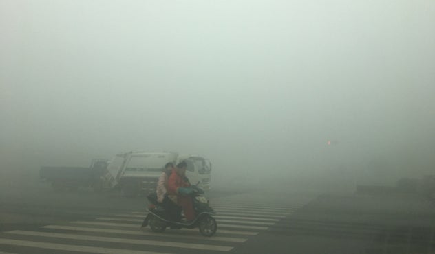 Motorcyclists ride through thick smog on January 9, 2017, in Zhengzhou, China.