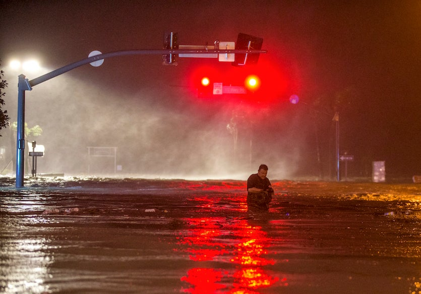Lanny Dean, from Tulsa, Oklahoma, takes video as he wades along a flooded Beach Boulevard next to Harrah's Casino as the eye of Hurricane Nate pushes ashore in Biloxi, Miss., early on Sunday morning, Oct. 8, 2017