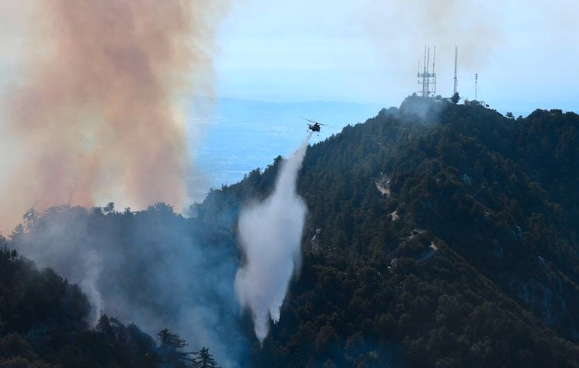 A helicopter drops water over a fire in the Angeles National Forest near Mt. Wilson Observatory, northeast of Los Angeles, California, on Oct. 17, 2017,