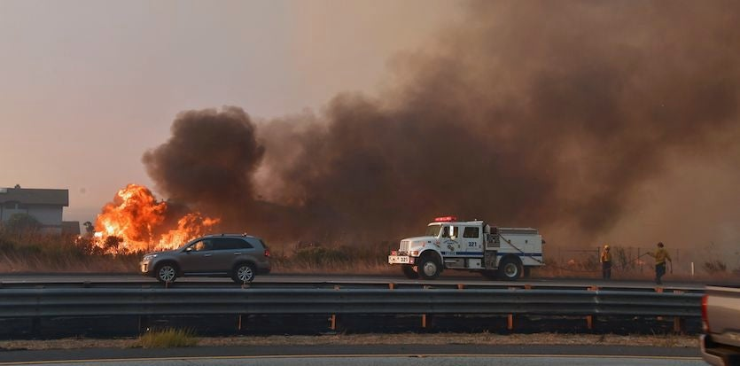 Vehicles pass fire burning on the south (coastal) side of U.S. Highway 101 in Mondos Beach, west of Ventura, California on Thursday, December 7, 2017.