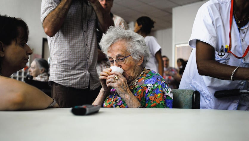 "A resident of the ""Montplaisir"" retirement home in the French town of Lyon has a drink in an air-conditioned room on August 18, 2009, during a visit from French Secretary of State for the Elderly Nora Berra (not pictured)."