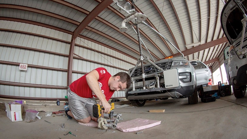 Graduate student Alex Erwin drills a pipe that will hold an instrument cluster on the University of Nebraska's newest storm chase vehicle.
