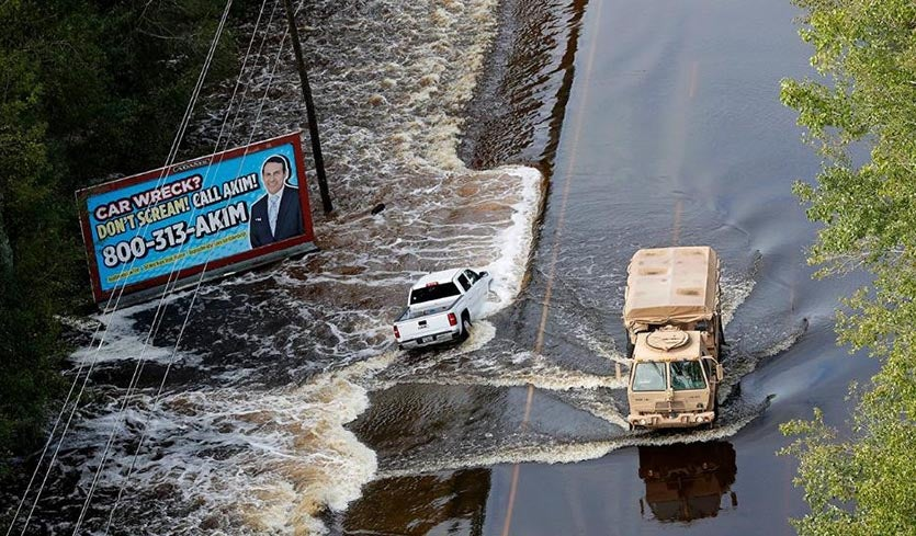 A National Guard vehicle drives past a truck washed off the roadway from floodwaters in Dillon, S.C., Monday, Sept. 17, 2018, in the aftermath of Hurricane Florence