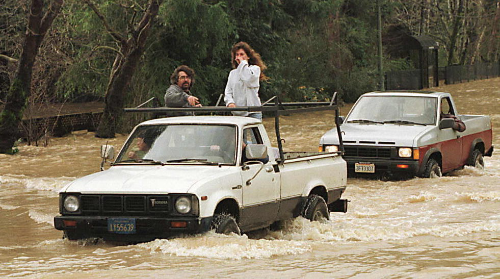 Two trucks cross a flooded road in Guerneville, Calif., on January 2, 1997