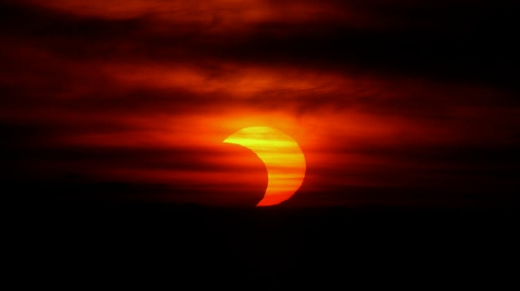 A partial solar eclipse behind thin clouds, photographed from near La Dole, Switzerland, in May 1994.